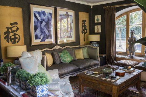 """Living Diseño interior inspirado en un estilo oriental, mezcla estilos que combinan perfectamente con los cuadros orientales """"laberinto Azul"""" y lo clásico del sofá y mesa de centro. Los muros empapelados en negro, son de la colección """"Revival""""."""